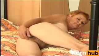 Ruda babcia masturbuje się na łóżku