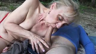 Laska klęczy i bierze kutasy do ust